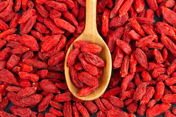 Spoon with Goji berries over red goji background. Healthy food concept.
