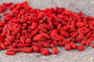Goji berries scattered on gray stone background. Selective focus.