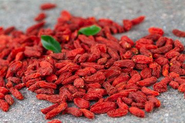 Dried Goji berries scattered on gray stone background. Selective focus.