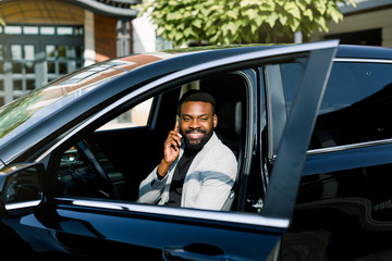 Cheerful African man in gey jacket sitting in car talking by the phone, office center on the background