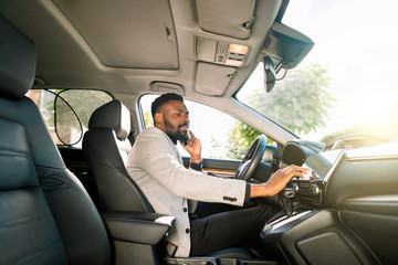 African businessman talking on mobile phone inside a car and touching the tablet. Young entrepreneur working during travelling to office in a luxury car.