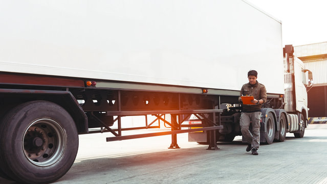 Truck driver asian holding clipboard inspecting safety vehicle maintenance checklist of modern semi truck.