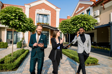 Three young elegant colleagues walking and discussing business matters outdoors. Caucasian man is using tablet, African man talking phone, Caucasian woman is speaking and smiling