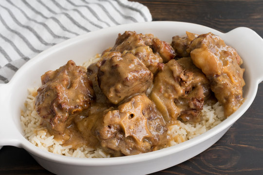 Southern Smothered Oxtails: Traditional Southern beef oxtails smothered in onion gravy and served over white rice