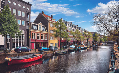 Fototapete - Netherlands Amsterdam. View at river Amstel with traditional houses at bank and boats at water canal. Scenic cityscape. Spring day with blue sky and white clouds.