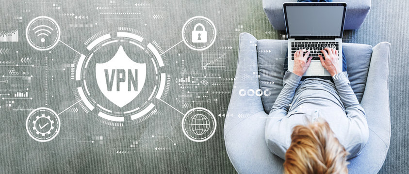 VPN concept with man using a laptop in a modern gray chair