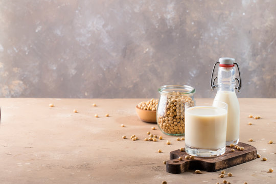 Soy milk and soy bean on gray table. Non-dairy milk concept. Vegan drink. Copy space