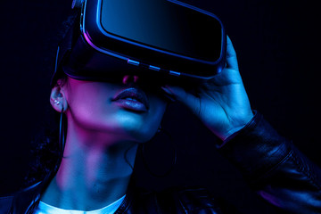 Young african american girl playing game using VR glasses, enjoying 360 degree virtual reality...