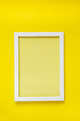 Empty  white frame on yellow texture of crumpled paper in the volume of horizontal lines hanging on  bright yellow wall.  Frame Concept. Flat lay. Blank Space