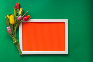 Beautiful tulip  flowers and white photo frame  on red  pattern texture of crumpled paper, green  background. Spring and Easter  Frame Concept. Flat lay. Blank Space