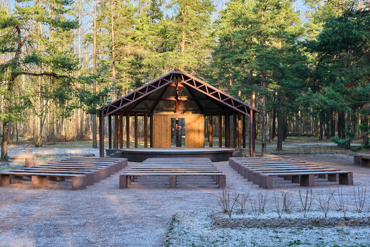 Wooden house stage for free musicians open air performances in pine forest in sunlight, in front of stage many benches covered with snow. Raising  culture of people, music for all, art theater in park
