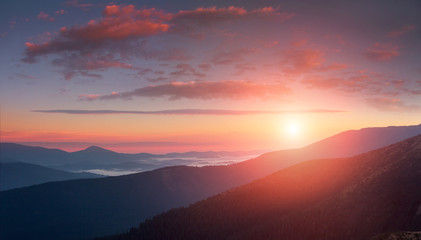 Keuken foto achterwand Ochtendgloren Panoramic landscape of colorful sunrise in the mountains. View on foggy hills covered by forest. Concept of the awakening wildlife.