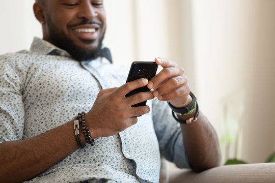 Guy sitting on couch closeup focus on hands holding smartphone
