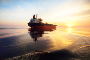 Large cargo ship sailing in an open sea. Golden sunset light, cloudscape. Freight transportation, nautical vessel, logistics, global communications, economy, business, industry, worldwide shipping