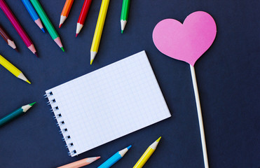 Notepad, heart made of paper and color pencils on a black background