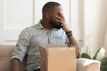 African guy feels stressed saw that goods in parcel damaged