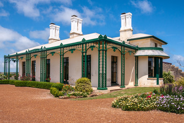 Stanley, Tasmania, Australia - December 15, 2009: Hightfield Historic Site. Closeup of White with green trim main house with tall chimneys with flowers up front under blue cloudscape.