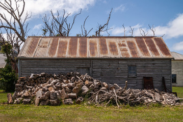 Stanley, Tasmania, Australia - December 15, 2009: Hightfield Historic Site. Heap of chopped brown firewood in front of gray wooden barn with rusty corrugated metal roof under blue cloudscape.