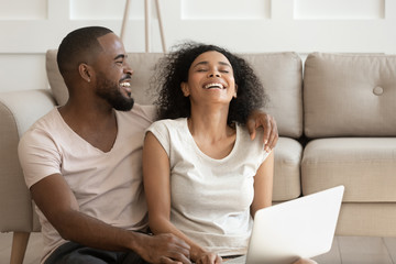 Cheerful african couple having fun using online websites at home