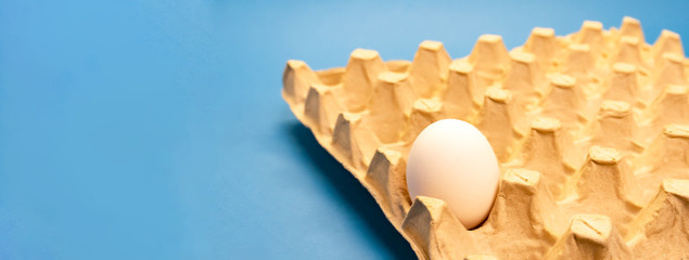 One white chicken egg in non recycable holder of the eggs on blue background. Eco and easter concept. Banner.