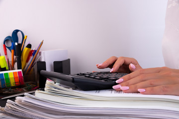 Photo of hands pressing calculator buttons over documents