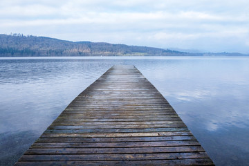 A long wooden jetty on a lake, jutting sraight out over a clear calm blue lake
