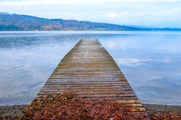 A long wooden jetty on a lake, looking out over a clear calm blue lake, winderemere, England,