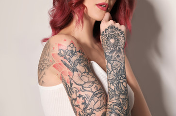 Beautiful woman with tattoos on body against light background, closeup