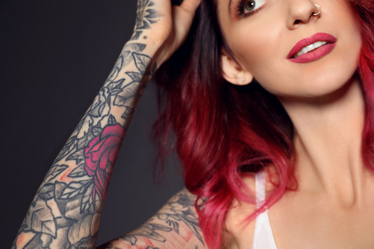 Beautiful woman with tattoos on arm against black background, closeup