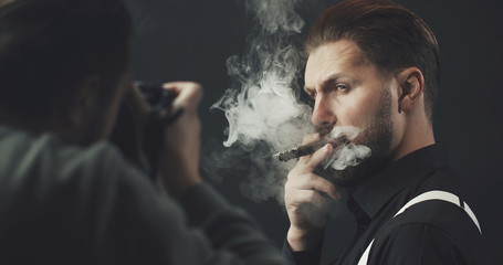 Photographer with camera shooting adult man smoking cigar over dark background, cropped shot