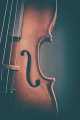 Violin detail with dark background vertical vintage