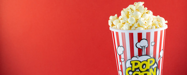 Butter popcorn in a red popcorn cup, snack in the house or cinema on a red background