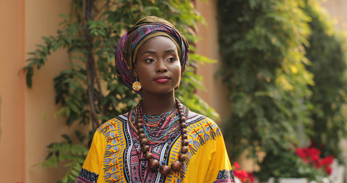 Close up of the face of the pretty young African woman in the traditional outfit looking at the side and smiling to the camera. Portrait. Outside.