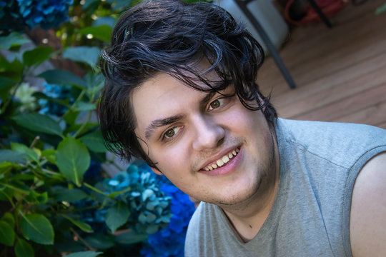 young man smiling on garden deck with gray shirt in summer