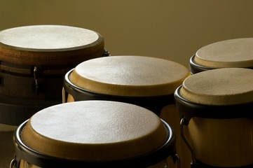 Closeup of bongo drums under the lights against a yellow background