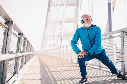An elderly man stretching outdoors and wearing headphones.