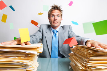 Stressed businessman holding onto the desk for support sitting between large piles of paperwork