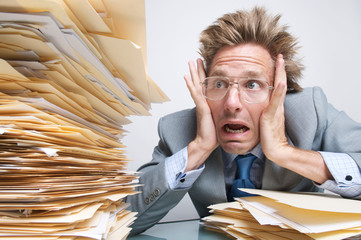 Stressed office worker looking with   shock at a massive stack of file folders on his desk