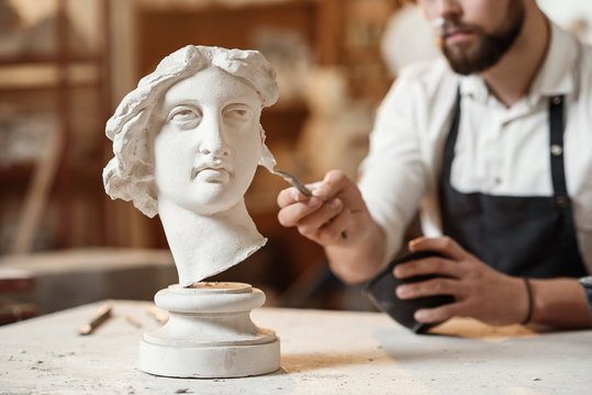 Skillful sculptor makes professional restauration of gypsum sculpture of woman's head at the creative workshop.