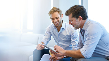 Young and mature businessmen smiling while using a digital tablet