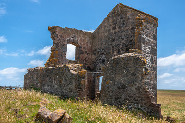 Stanley, Tasmania, Australia - December 15, 2009: Hightfield Historic Site. Part of gray stone building ruins set in green-yellow meadow against blue sky with white clouds.