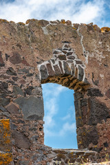 Stanley, Tasmania, Australia - December 15, 2009: Hightfield Historic Site. Closeup of window hole in gray stone building ruins against blue sky with white clouds.