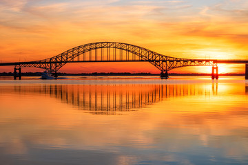 Steel tied arch bridge spanning a bay with crystal clear reflections in the water at sunset. Fire...
