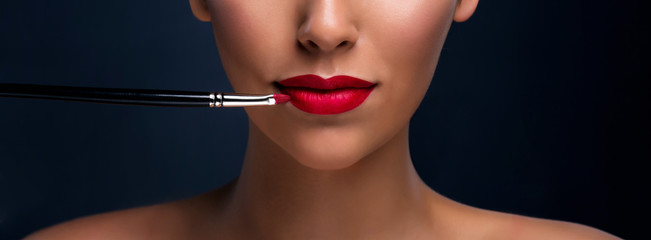 Close up of red mat lips with cosmetic brush. Professional makeup.