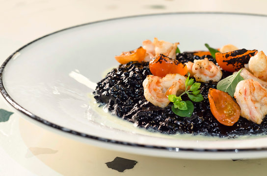rice with cuttlefish ink, octopus, mussels, squid, shrimp. prawns and grilled tomatoes on a large white plate in a restaurant. Italian black risotto with seafood. national dishes of italy.