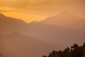 Layers of mountains in golden light rays at sunset in the Himalaya above Kathmandu Valley, Nepal.