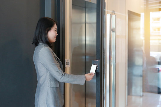 Door access control - young officer woman holding a key card to lock and unlock door for access entry.