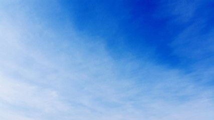 The blue sky cloudscape shot with blending clouds.  Beautiful blue space with just a white cloud to use as a background in your designing  space. Royalty free stock picture.