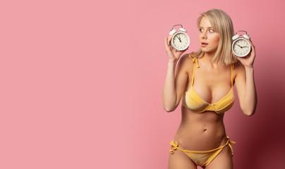 blonde woman in yellow bikini with alarm clocks Wall mural
