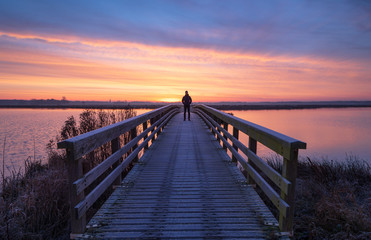 A man on a wooden bridge enjoying the view during a tranquil sunrise.